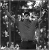 "Eldrick ""Tiger"" Woods thrust his arms triumphantly in the air"